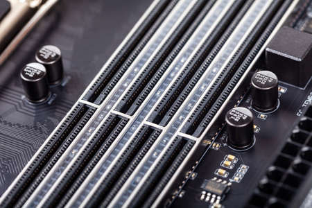 Closeup on empty RAM slots on a modern black silver motherboard. Ddr4, ddr5 random access memory stick slots, ram placing order. Macro electronics shot, technology, simple pc components, shallow dof