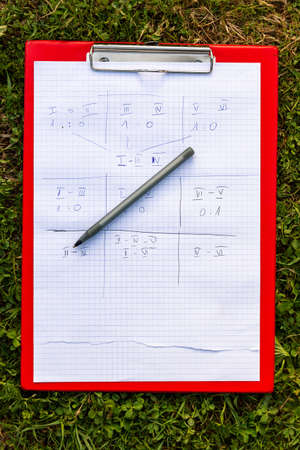 Team game paper scoreboard a pen and a holder laying on the grass outside. Numbered team results, notes written on paper, outdoor group activities and group sports simple abstract concept, nobody