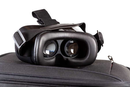 VR travel concept, simple modern virtual reality goggles, glasses headset laying on top of a suitcase, travel bag. Cyber travelling, adventure and sightseeing in augmented reality abstract concept 免版税图像 - 157928919