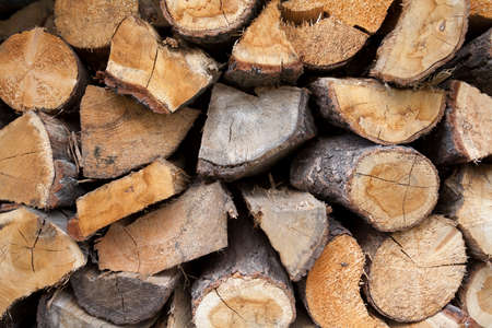 A pile of cut fire wood abstract texture. Lots of stacked wooden logs piling, tightly alligned. Wallpaper, background. Lumber, timber concept. Vertical shot, wall of wood