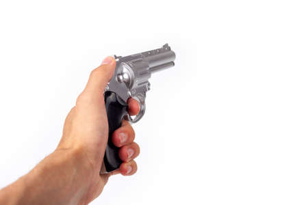 Hand holding a silver gun pulling the trigger, revolver in hand pointed away. Wild west handgun silver bullet pistol, dangerous shooter concept. Man pulling the trigger closeup isolated on white Stock Photo
