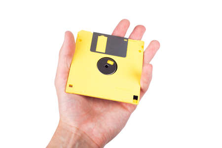 Single bright yellow floppy disk, pastel computer diskette being held in hand, shown, presented to the viewer. Old tech vintage historical data storage save icon concept. Isolated on white, copy space