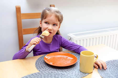 Young happy primary school european girl eating her food by herself, grabbing a last bite on a fork, empty plate and a mug before her. Children eating, self-reliant kids home activities, family meal