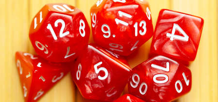 Lots of red RPG game dice extreme closeup wide shot, banner. Role playing board games symbol, simple polyhedral dice set scattered, showing random numbers. Nerd, geek culture, math probability concept Stock Photo