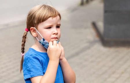 一个累了,不快乐和担心的焦虑的小女孩,拿走一个保护的反病毒面罩,年轻学校孩子画象。Covid 19,电晕病毒,保护,儿童,大流行概念的结束