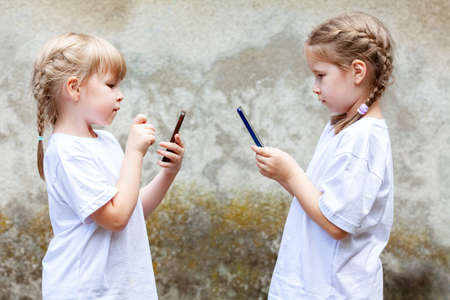 Two little girls, sisters or friends using their smartphones, children texting on their mobile phones facing each other. Kids and modern technology, addiction, dependence, simple lifestyle concept