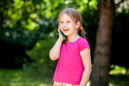 Happy cheerful little girl, child talking on phone laughing, young kid with a smartphone, phone call outdoors, portrait, copy space Telecommunication, mobile phone communication concept lifestyle shot