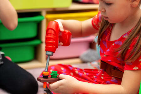 Little girl, young school age child playing with construction tool toys, dream job, future occupation dreams abstract concept, equality. Kid playing with toy electric screwdriver, indoors lifestyle