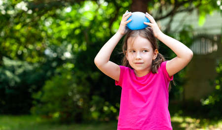 Little child, girl smiling playing with a water balloon outdoors, outside portrait, copy space. Kid holding a balloon filled with water over her head, fun and leisure activities lifestyle concept