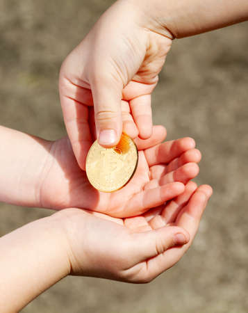 Children passing a gold bitcoin coin from hand to hand. Kids passing around a bit coin symbol in hands, closeup. Cryptocurrency, digital currency transfer, payment, donation gift abstract concept Imagens