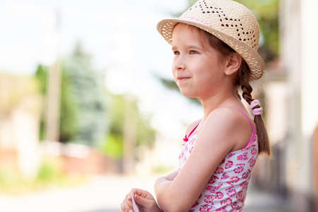 One happy cheerful joyful little girl alone, lone child in a sun hat smiling, portrait, copy space, lifestyle shot. Summer, daylight, hot weather. Vacations, young school age kids and holidays concept