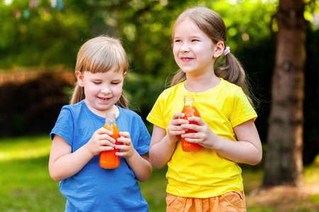 Two happy young cheerful little school age girls holding opened glass bottles full of healthy orange carrot juice fruit drink smiling, outdoors portrait, healthy eating, simple lifestyle concept