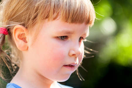Young child, little girl simple portrait, face expression detail extreme closeup, outdoors scene, blurred background. School age caucasian child deep in thought, sunlight, summer, lifestyle, side view Imagens