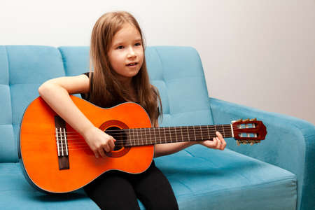 Young child, little school age girl playing classic acoustic guitar, practicing musical instrument sitting on the sofa Simple music education at home, child's hobbies and talents, portrait, interior. Imagens