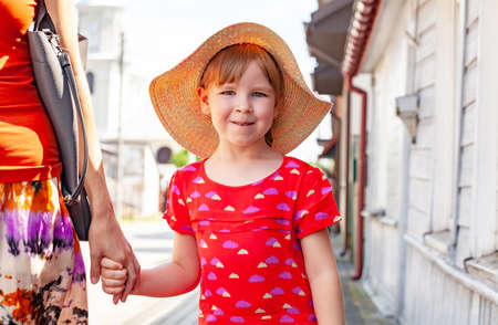 Happy cheerful little school age girl, young child walking by the hand with her mother, outdoors portrait, closeup. Family walk, parent togetherness, child's happiness and joy simple lifestyle concept
