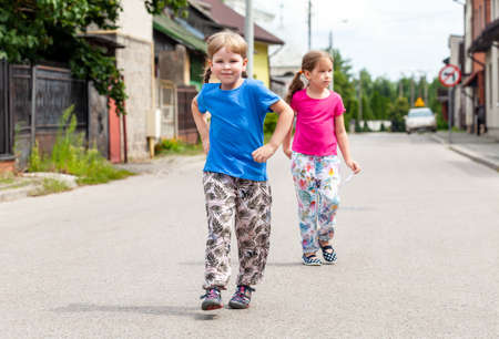 Two smiling little girls walking on the street, happy siblings stroll outdoors alone by themselves Cheerful children walking in the middle of the street, lifestyle. Kids going shopping, independence Imagens