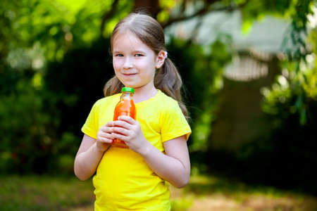 Happy young child, one little girl alone holding a bottle of healthy orange carrot juice smiling, outdoors park portrait, copy space blurred background Healthy drink products, simple lifestyle concept