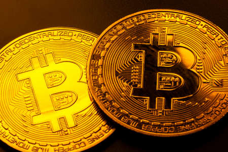 Two shiny gold bitcoin coins macro, extreme closeup. Golden cryptocurrency symbol up close, decentralized finance, digital assets wealth, bitcoin crypto currency market financial concept, trading