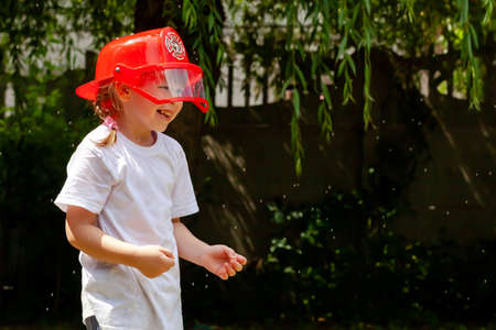 A little young school age girl wearing a red firefighter toy helmet being sprayed with water, outdoors, child playing outside, portrait Future occupation child's dream job abstract concept, copy space