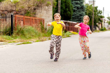 Happy young children on the town street, two joyful cheerful little school age girls jumping, walking on the street together Siblings, sisters or friends two active kids happily dancing in the streets