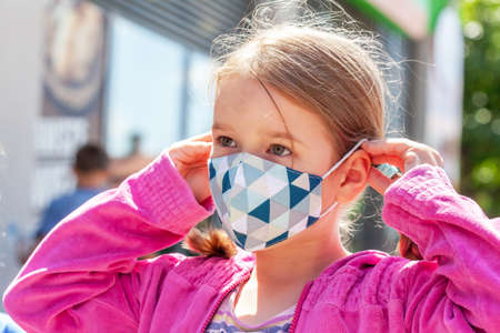 Little girl, young school age child taking off or putting on a protective medical face mask, portrait, closeup, outdoors new normal lifestyle shot. Kid wearing a facemask. Imagens