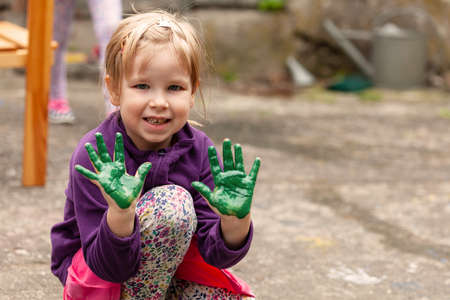 Young happy child, joyful cheerful little school age girl showing both of her hands covered in green paint, outdoors portrait, copy space, lifestyle shot. Active kids and art, creativity, happiness