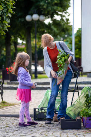 Little girl, child and her mother buying vegetables together at the local vegetable market. Family shopping lifestyle concept, healthy food, farmer shop, buying fresh vegetables, doing groceries