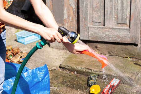 Mother washing childs toys using a water hose, outdoors lifestyle scene. Cleaning children's toys with water outside, summer, sunny weather, closeup. Disinfecting and washing plastic toys concept