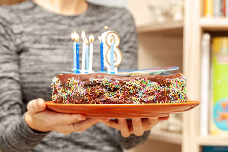 A woman bringing in a delicious homemade birthday cake, brown cocoa chocolate cake with sprinkles, icing and candles, holding a plate. Childs birthday, sweet food, closeup. Birthday cake on a plate Imagens