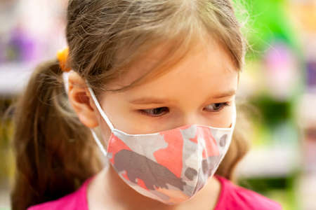 Young child, little girl, kid in colorful modern fabric protective face mask portrait, closeup, shallow depth of field, blur. Child wearing a facemask looking down, extreme closeup, face up close Imagens