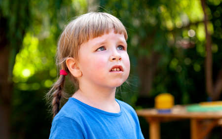 Worried child, anxious little school age girl looking up, portrait, face grimace closeup, outdoors Anxiety, uncertainty psychological concept, lifestyle. Troubled and distressed caucasian kid up close
