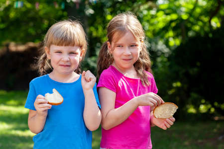 Two happy little girls eating slices of bread with butter smiling, outdoors portrait. Kids, sisters, children eating food outside, lifestyle shot, sunny weather. Nutrition, healthy eating concept Imagens