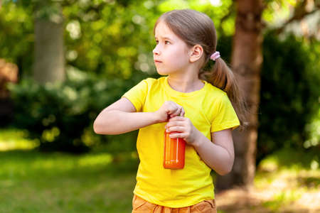 School age young child, happy little girl opening a glass bottle full of healthy orange carrot juice, simple outside outdoors portrait closeup, nature, copy space Healthy active kids lifestyle concept