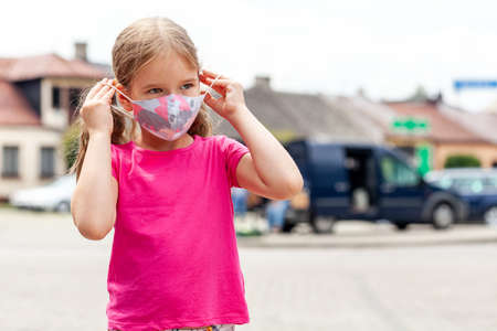 Little girl, one school age child putting on or taking off a colorful modern protective face mask, outdoors lifestyle potrait, town area, copy space. Covid 19 pandemic, coronavirus safety and children Imagens