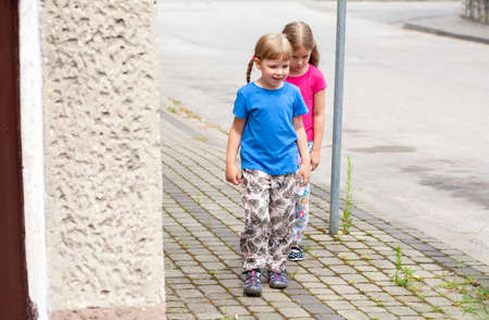 Two happy little girls, school age children walking on the sidewalk near a street on their own Young kids, siblings or friends strolling together, outdoors lifestyle shot, leisure, daytime, copy space
