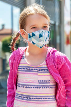 Happy joyful little girl, school age child wearing a protective face mask smiling, portrait, vertical. Kid in a colorful facemask, corona virus, covid 19 protection, children safety, lifestyle shot