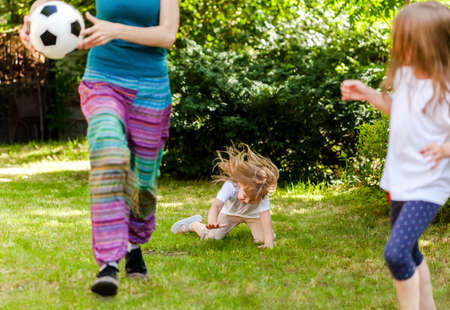 Child falling down running, playing ball with family in the garden, injury concept. Kids outdoors sport activity accident, fall on the grass during outside recreational activities, playtime safety