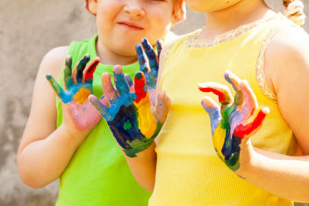 Two happy creative school age children, colorful painted hands, kids with hands covered in multi colored paint Arts and crafts, creativity, sensory integration, kids having fun, art education concept