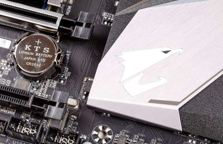 Z390 Aorus Pro Wifi high end motherboard, Gigabyte Aorus logo and bios cmos battery detail, macro, KTS cr 2032, closeup, top view, from above, pc components