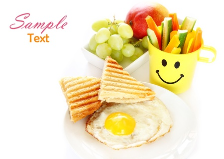hungry kid: breakfast including egg, toast, fruits  Stock Photo