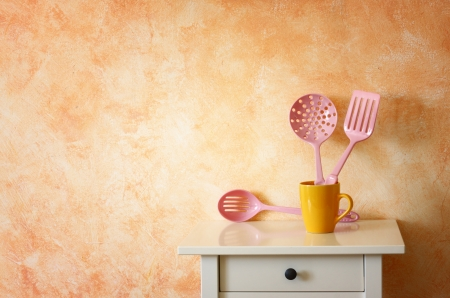 Kitchen cooking utensils  plastic spatulas in yellow cup against rustic terracotta wall  photo