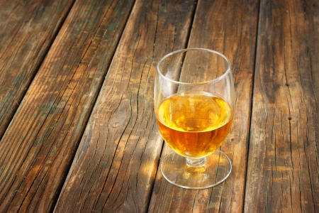 Scotch on wooden background with copyspace  An old and vintage table with glass of liquor  photo