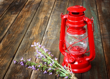 red vintage kerosene lamp, and sage flowers on wooden table  fine art concept   photo