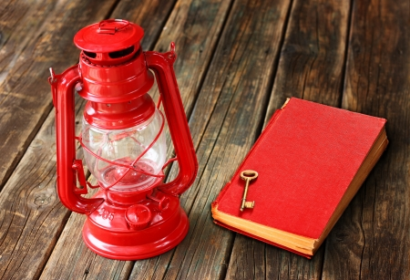 kerosene lamp: red vintage lamp and red antique book on wooden table  vintage still life design