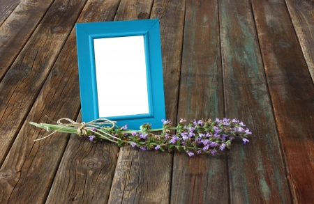 classic blue picture frame on wooden table and sage plant decoration photo