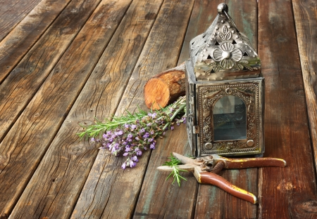 kerosene lamp: vintage oriental lamp, sage plant and garden scissors on wooden table  still life concept  fine art
