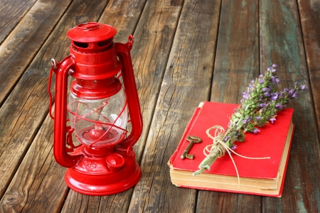 vintage red lantern and red book on wooden table  photo