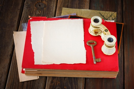 antique binoculars: vintage binoculars on red ancient book with blank page for text  nostalgic vintage background