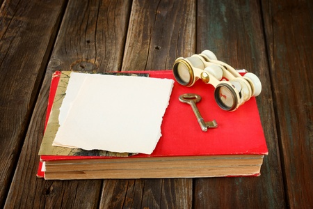 vintage binoculars on red ancient book with blank page for text  nostalgic vintage background  photo
