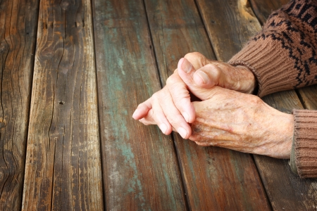 sad: close up of elderly male hands on wooden table  Stock Photo